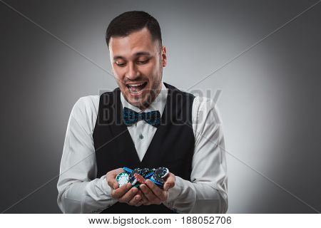 Poker player taking poker chips after winning. Studio shot on gray background. Emotions happy win