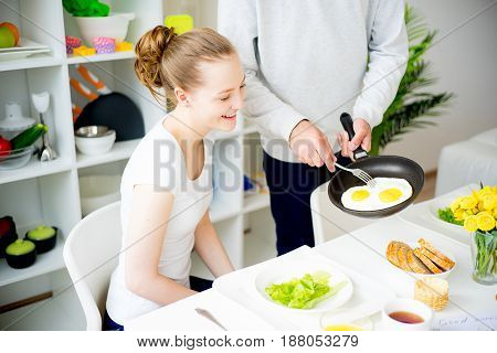 Couple eating breakfast early in the morning in the kitchen
