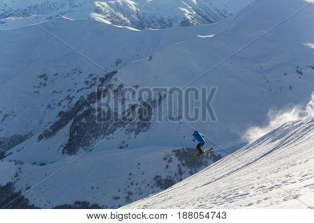 Skier Skiing On Fresh White Snow With Ski Slope On Sunny Winter Day