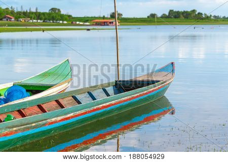 WOODEN BOAT ON THE LAKE with bue sky and cloud.