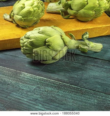Vibrant green artichokes on dark rustic textures with a place for text, square photo