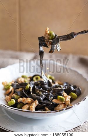 Black ink pasta with chicken breast and green olives