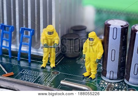 Two toy technicians are repairing, cleaning and diagnosing a motherboard.