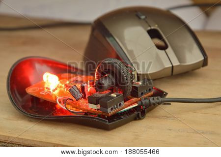 computer mouse separated parts with red light on wooden board