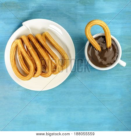 Plate of churros, traditional Spanish, especially Madrid, dessert, particularly for Sunday breakfast, with cup of hot chocolate, shot from above on turquoise table with a place for text, square photo