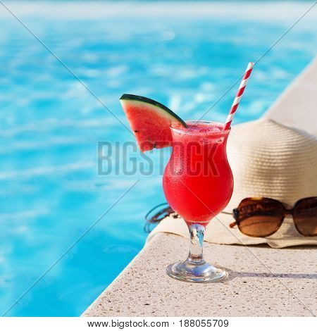 Water-melon fresh fruit smothie drink with sunglasses and straw hat on swimming pool border - holiday concept
