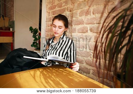 Girl student at home at the table studying reading book