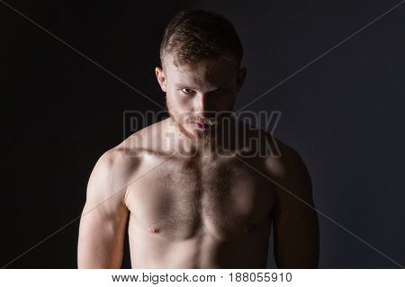 Bearded man with muscular body on black background