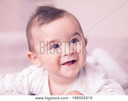 Portrait of giggling baby boy on isolated background.