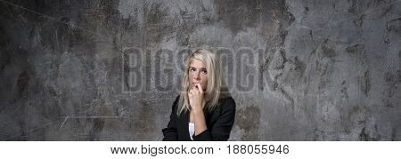 Portrait of a pensive young woman thinking dreaming has many ideas looking at the camera. Positive human expression of emotions, expressing a sense of life. Style