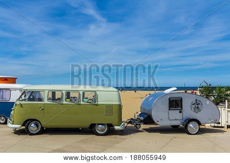 Scheveningen beach the Netherlands - May 21 2017: Green VW kombi camper wagen and teardrop trailer at Aircooled classic car show