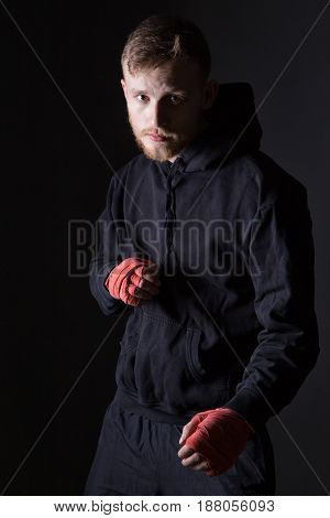Fighter bearded man wearing black tracksuit on black background