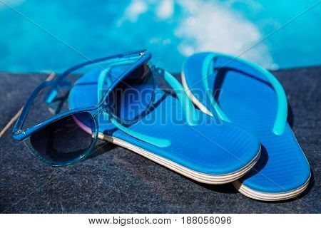 Blue slippers and sun glasses near swimming pool - holiday concept