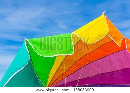 rainbow colour beach umbrella with sunning blue sky background