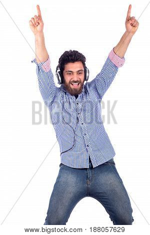 smiling excited beard yung man listening to music and raises his hands guy wearing blue shirt isolated on white background