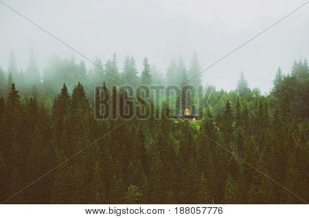 Little house on a green mountain slope, natural landscape vintage background. Foggy morning