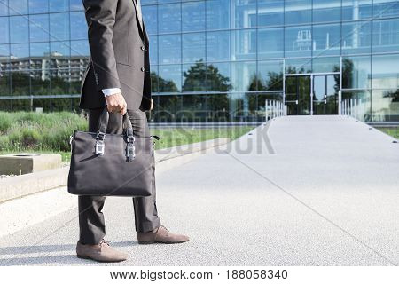 Anonymous businessman or worker standing in black suit with leather handbag or laptop case in his hand standing on the road at the entrance in front of a glass office building.