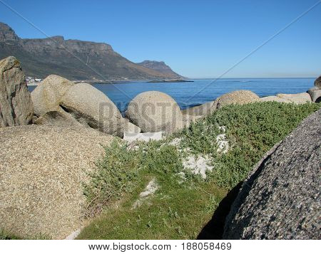 FROM CAMPS BAY, CAPE TOWN, SOUTH AFRICA, HUGE BOULDERS AND GRASS IN FOR GROUND AND MOUNTAIN IN BACK GROUND 24mjhg