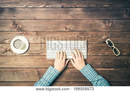 Female hands white keyboard and coffee cup on table