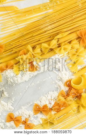 A photo of spaghetti, penne, and bowtie pasta with traces of flour, shot from above on a white marble texture with a place for text