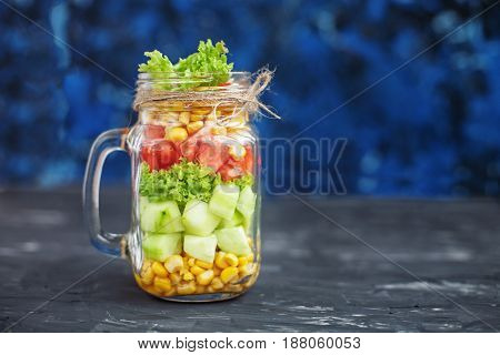 Salad with tomatoes and corn and cucumbers and lettuce. Blue background. Healthy food Diet Detox Clean Eating or Vegetarian concept