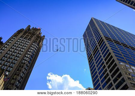Airplane Flying over buildings in Chicago, USA.