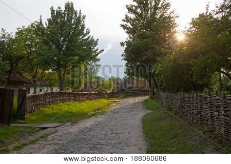 The road paved with stones in the Ukrainian village. Wicker fences and straw thatched roofs along the road. Museum of Folk Architecture near Kyiv.