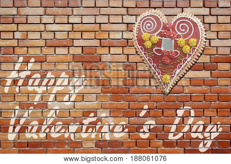 The brick wall with message for the Valentine's day and traditional heart-shaped cookie hanging on it