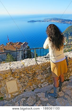 The girl watches the seascape from the viewpoint on the hilltop of Eze village France.
