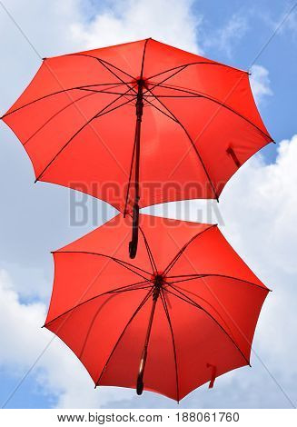 Two red umbrella flying in the wind