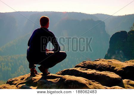 Resting Man At The Top Of Rock With Aerial View Of The Deep Misty Valley Bellow