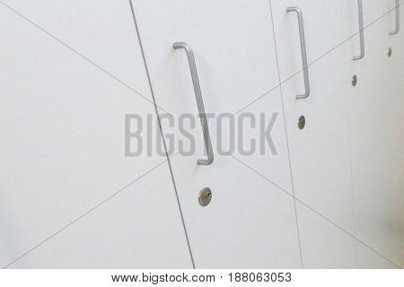 Detail Of Door Handles Of White Lockers