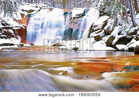 Winter Snowy Boulders And Cascade Of Waterfall.