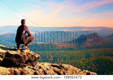 Climbing Adult Man At The Top Of  Rock With Beautiful  Aerial View Of The Deep Misty Valley Bellow