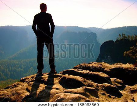 Tall Hiker On Peak Of Sandstone Rock Watching Over The Misty And Foggy Morning Valley To Sun. Beauti