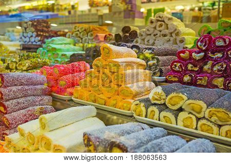 The tasty rolls of Turkish delight (rahat lokum) with nuts dry fruits coconut powder nougat and other ingredients in the candy shop of Kemer Turkey. poster