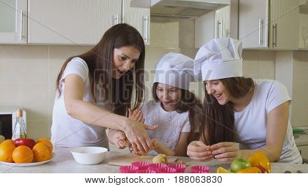 Sisters with Mom is Cooking in Kitchen.