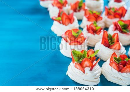 A small meringue Pavlova dessert with strawberry slices garnished on blue background.