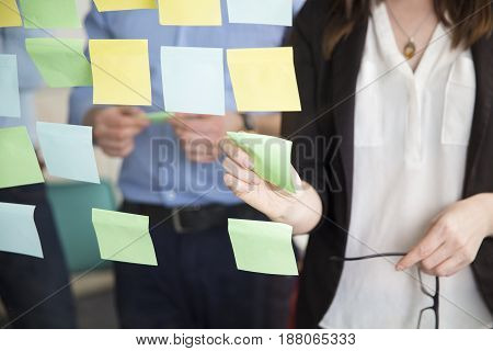 Midsection of businesswoman sticking note on glass while standing by executive in office
