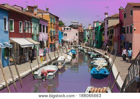 BURANO, ITALY - MAY 23, 2017: Romantic sunset with boats on Burano island