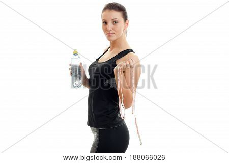 beautiful young girl in black sports suit stands sideways and holding a bottle of water and a measuring tape isolated on white background