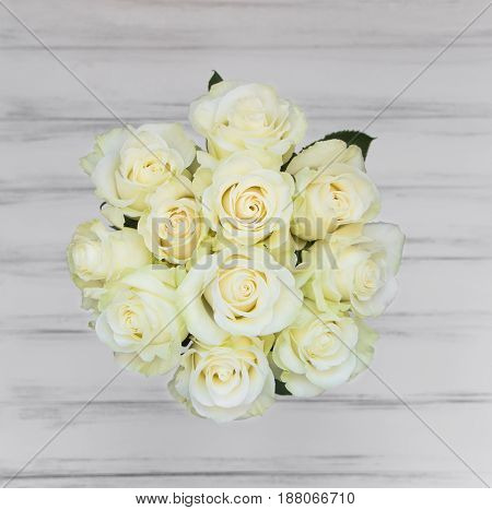 Perfect bouquet of creme luxury roses for wedding birthday or Valentine's day. White old wooden background top view flat lay