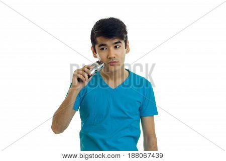 cute young guy with thick black hair stands straight and shaves his beard is isolated on a white background close-up