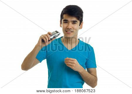 smiling handsome guy in the blue shirt stands up straight and holding in his hand shaving Clipper is isolated on a white background