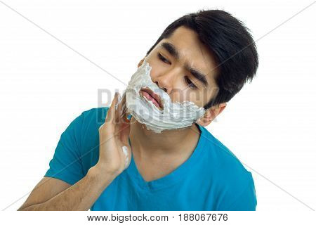 Portrait of a handsome guy with black hair causes shaving foam on your face closeup isolated on white background