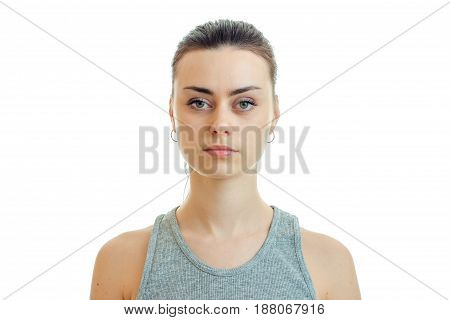 Portrait serious pretty girl that looks straight into the camera close-up isolated on white background