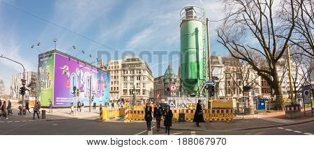 DUESSELDORF, GERMANY - MARCH 13, 2017: Unidentifeied pedestrants pass the construction area at the end of famous Koenigsallee.