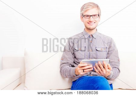 Guy wearing glasses sitting on the white couch holding tablet and smiling