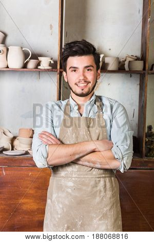 potter, tools, ceramics art concept - smiling brunette male with a beard dressed in an apron, ceramist with baked utensil at workshop, Mexican, Hispanic, Latino, Caucasian
