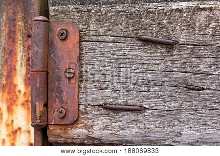 Old vintage wooden hinge on a fence with nails